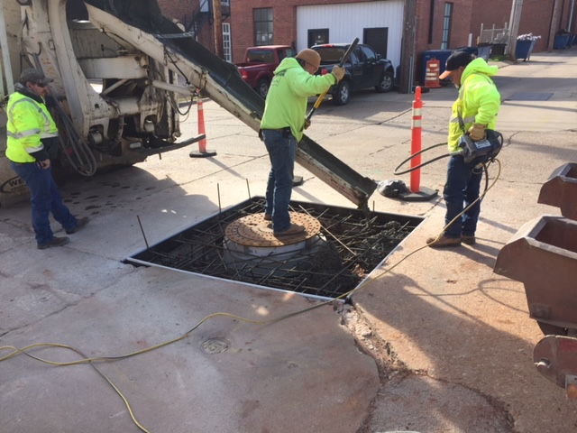 Reconstructing the concrete around the manhole lid. Man standing on manhole lid guiding concrete into the hole.
